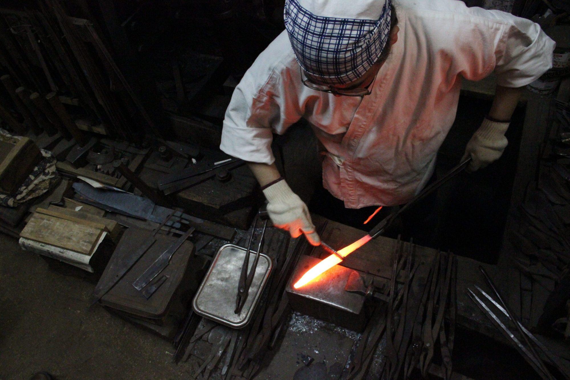 Japanese blacksmith making kitchen knives