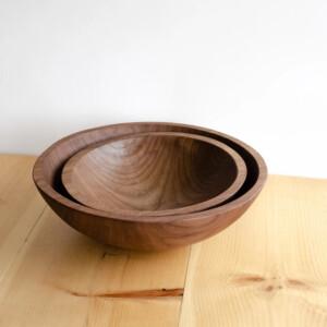 Handmade walnut wooden bowls on white background stacked