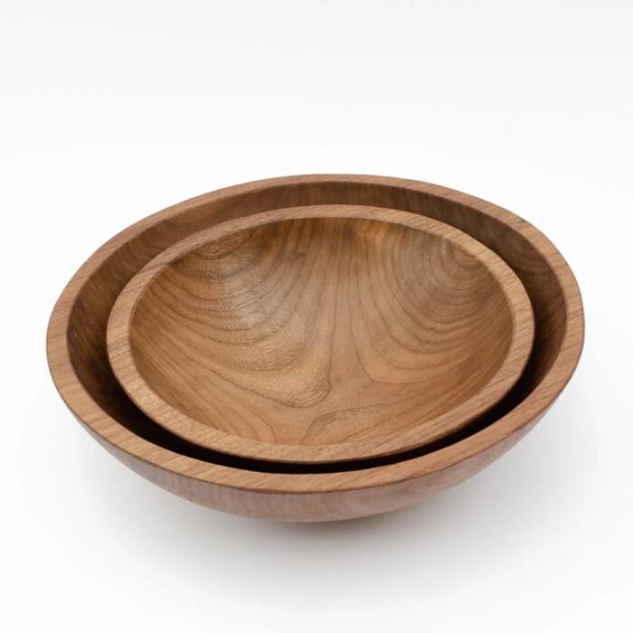 Handmade walnut wooden bowls stacked on white background