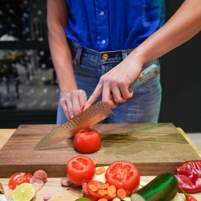 woman cutting with sakai kyuba blue chefs knife